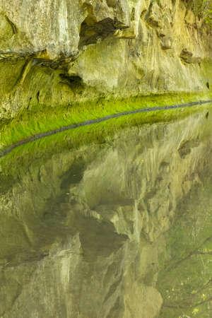 A calm reflective creek next to a cliff. Stock Photo