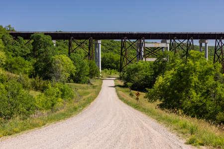 A gravel road leading to a high trestle railroad bridge.