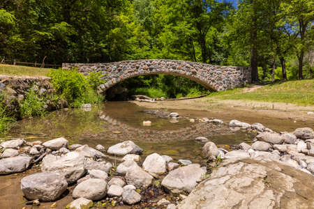 Stone Arch Footbridge Over A Creek In The Woods