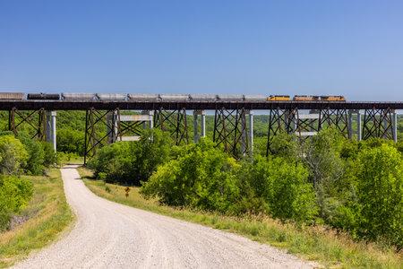 Freight Train Traveling Across High Trestle Bridge Stock Photo
