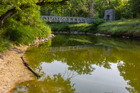 Swing Bridge Over A River In The Woods