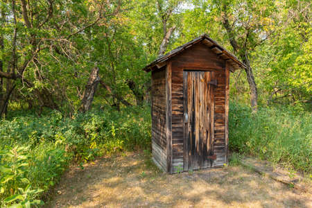 An old wooden outhouse in the woods.