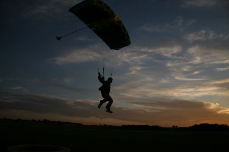 swooping: Professional skydiver landing at sunset