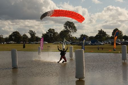Professional skydiver swooping over a pond Stock Photo