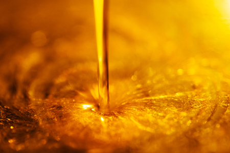 Orange liquid and viscous stream of motorcycle motor oil like a flow of honey close-up.