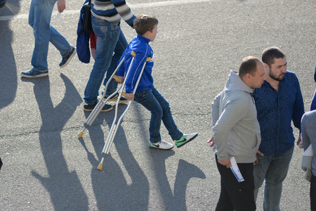 MINSK, BELARUS - MAY 23, 2018: Little fan on crutches with a leg injury before the Belarusian Premier League football match between FC Dynamo Minsk and FC Bate at the Tractor stadium. Editorial
