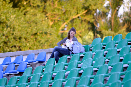 MINSK, BELARUS - MAY 23, 2018: Young mother with her baby on the stadium podium during the Belarusian Premier League football match between FC Dynamo Minsk and FC Bate at the Tractor stadium.
