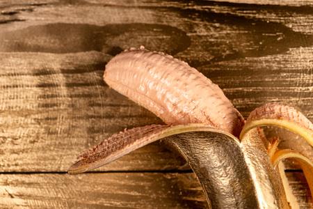 Gold peeled banana on wooden background . Stock Photo