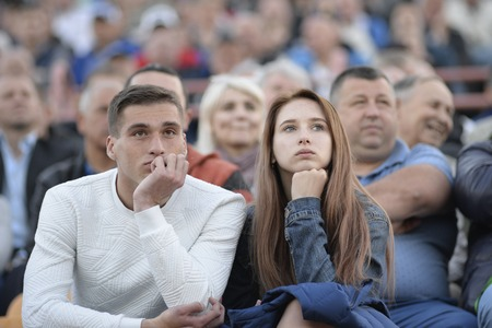 MINSK, BELARUS - MAY 23, 2018: Fans - man and woman looks game during the Belarusian Premier League football match between FC Dynamo Minsk and FC Bate at the Tractor stadium.
