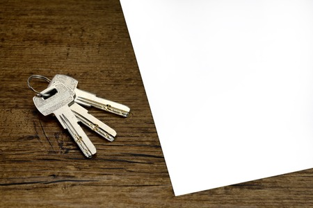 indenture or pact or contract blank for rent a apartment and 3 silver keys on wooden table