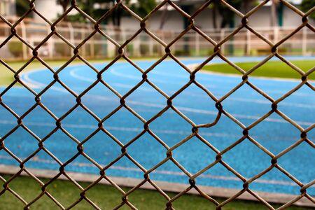 Valla de malla metálica alrededor de la pista de atletismo azul en Bangkok, Tailandia Foto de archivo