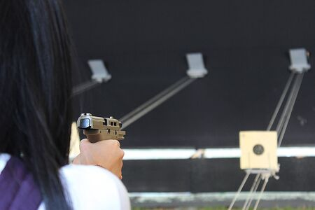 A woman firing a short gun in the shooting range