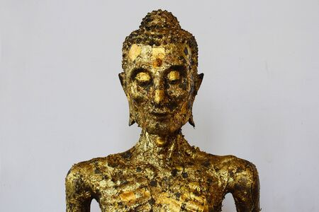 Self-mortification Buddha statue with gold leaf attached to the body in a Thai temple at Bangkok, Thailand