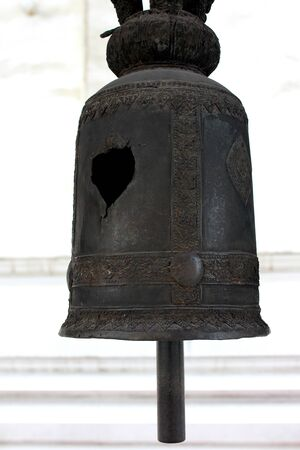 A black metal bell broken into a hole hanging in a thai temple, Bangkok, Thailand Stock Photo