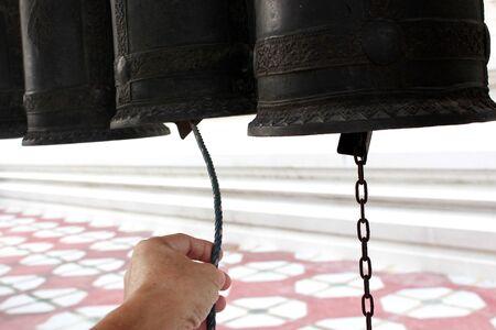 Knocking black metal bell at the thai temple, Bangkok, Thailand