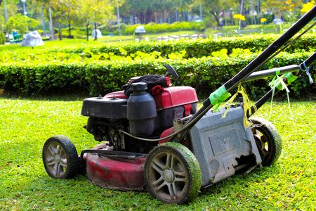 Old red lawn mower placed on the lawn in the park Imagens
