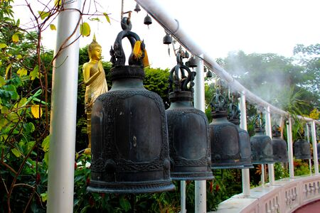 Black metal bells hung in row in thai temple and there is golden buddha statue behind them, Bangkok, Thailand