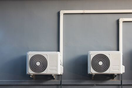 Two compressors of air conditioner placed on the wall outside the building Archivio Fotografico