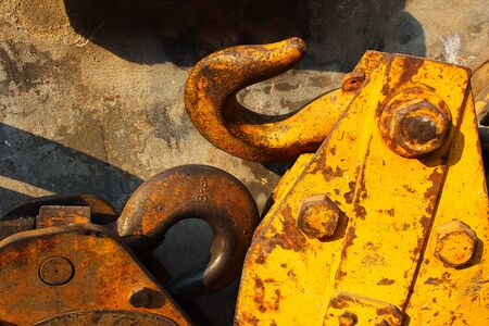 The old and rusty metal hooks of the forklift that was placed beside the wall