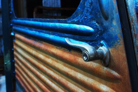 An antique door handle of the rusty old car