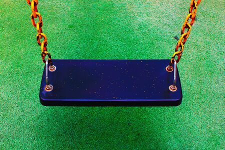 Steel swing chair on the artificial turf playground Stockfoto