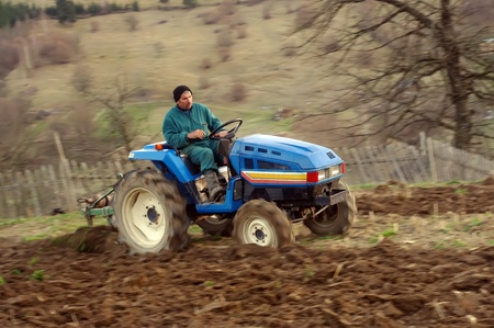 earth moving equipment: man on tractor at work tilling