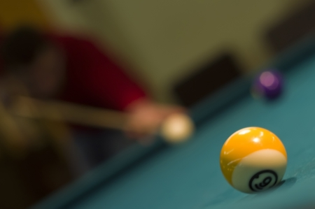 billiards tables: snooker ball and out of focus player in background  Stock Photo