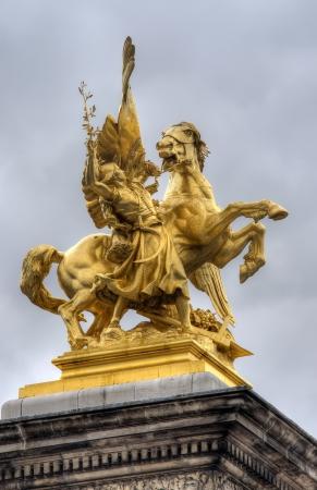 golden statue on Pont Alexandre Bridge, Paris, France photo