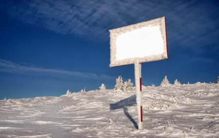 caked: mountain winter landscape with empty billboard and blue sky Stock Photo