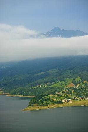 fresh landscape of mountain above clouds and lake photo