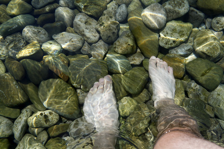 feet in clear sea of water full of stones photo