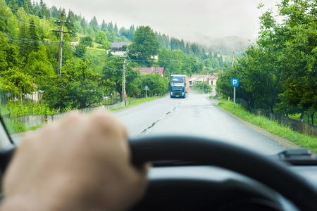 view of road and hand on wheel of car driving, focus on background Stok Fotoğraf