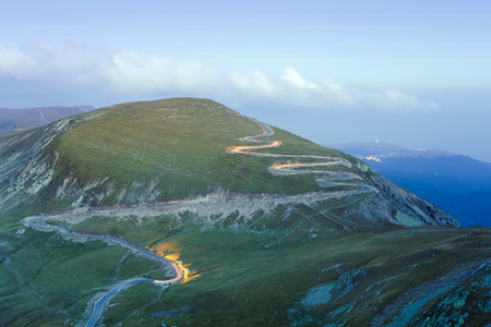 curved road in mountains of Parang, Romania. Transalpina at night with car trails, long exposure.
