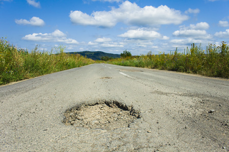 big hole cracked in the asphalt, road view Stock Photo
