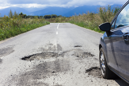 car and cracked asphalt with holes in the road