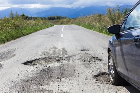 samochód i pęknięty asfalt z dziurami w jezdni
