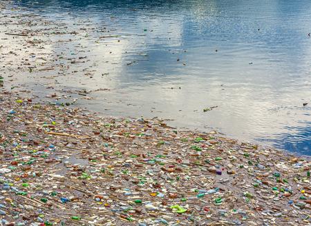 Contaminación del lago con bolsas de plástico y desechos tóxicos en el agua. Foto de archivo
