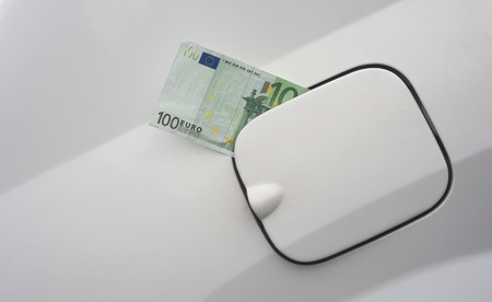 euro banknote in the fuel tank of car. concept of expensive gas