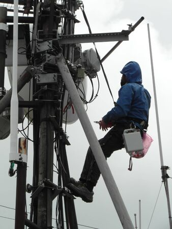 man worker on a pole. safety working in power industry Reklamní fotografie
