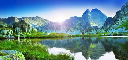 mountain lake in Retezat National Park, Romania. Lens flare added for sun effect