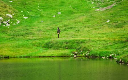 man walking in nature. green meadow and lake