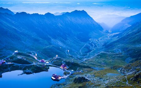 Balea lake and Transfagarasan road in Fagaras mountain. Romania at sunset Stok Fotoğraf