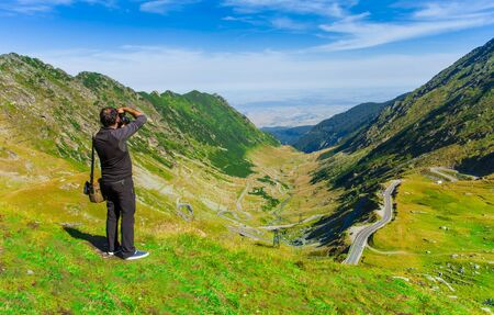photographer man taking photos in nature mountain landscape. Fagaras, Romania