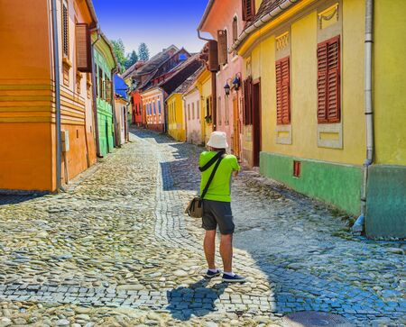 tourist taking photos in Sighisoara medieval city. Romania Stok Fotoğraf