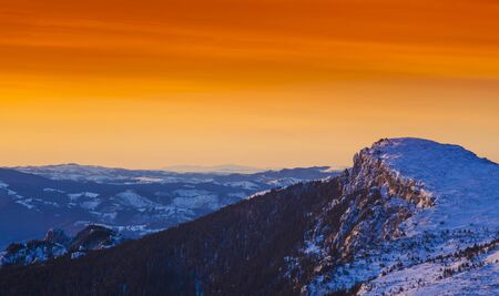 golden sunset in winter mountain landscape. Ceahlau, Romania
