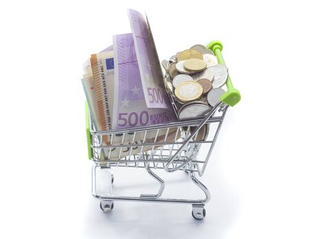 shopping cart full of money banknotes and coins for shopping. isolated on white