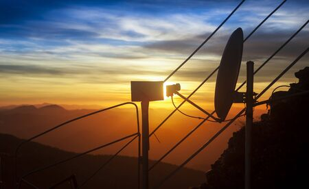 satelite antenna for tv and beautiful sunset on mountain