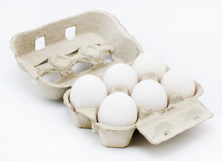 placed: six white eggs in box placed on white background