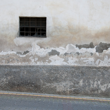 destructed: old wall with window and destructed stucco