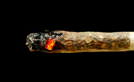 smoldering: Smoldering marijuana joint isolated on black background